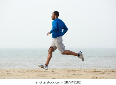 Healthy young black man jogging at the beach