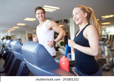 Healthy Young Couple Doing Running Exercise on Treadmill Device Inside the Gym with Happy Facial Expressions.