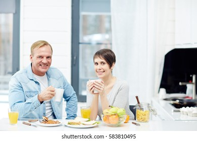 Healthy young couple eating breakfast at home