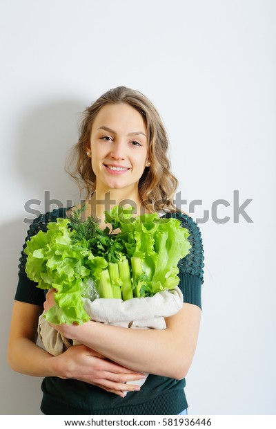 Healthy young female holding a bag of greens and salad leavs