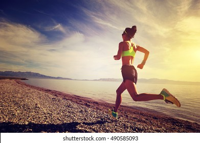 healthy young fitness woman trail runner running on sunrise seaside