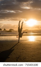 Healthy young man doing a handstand on one arm at the beach at sunset; freedom, recreation, happiness, joy, enjoyment; Oregon, Bandon