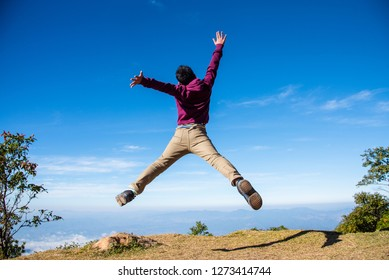 Healthy young man jumping in mid-air with beautiful mountain background.Freedom and success concept.