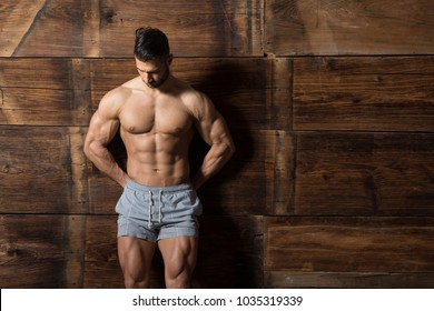 Healthy Young Man Standing Strong Against a Wooden Wall and Flexing Muscles While Wearing Sports Shorts - Muscular Athletic Bodybuilder Fitness Model Posing After Exercises - a Place for Your Text