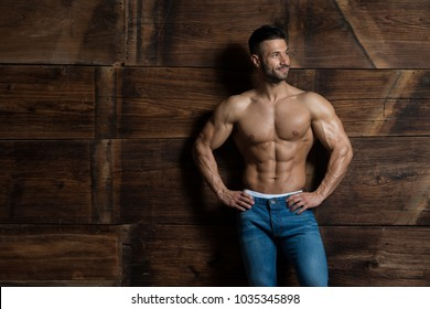 Healthy Young Man Standing Strong Against a Wooden Wall and Flexing Muscles While Wearing Blue Jeans - Muscular Athletic Bodybuilder Fitness Model Posing After Exercises - a Place for Your Text