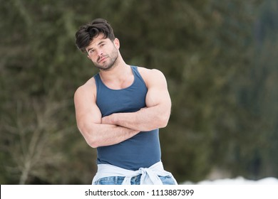 Healthy Young Man Standing Strong Flexing Muscles While Wearing Blue Jeans - Muscular Athletic Bodybuilder Fitness Model Posing Outdoors - a Place for Your Text
