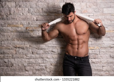 Healthy Young Man Standing Strong Against a Brick Wall and Flexing Muscles While Wearing Jeans Shorts With Towel - Muscular Athletic Bodybuilder Fitness Model Posing After Exercises