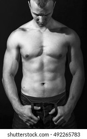 Healthy young man with strong arms and muscular male torso. Black background.  Fitness concept