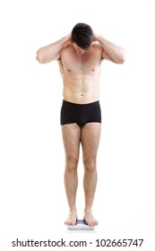 Healthy young man with a weight scale. Isolated over white background