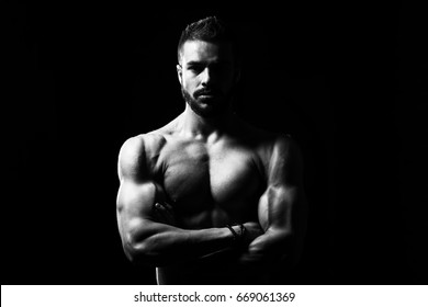 Healthy Young Model Standing Strong in the Fitness Center and Flexing Muscles - Muscular Athletic Bodybuilder Man Posing After Exercises