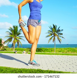 healthy young pretty mixed race woman stretching her leg during exercise on running trail near ocean right before a work out.