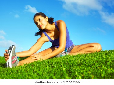 healthy young pretty mixed race woman stretching her leg during exercise in grass right before a work out. Horizontal shot.