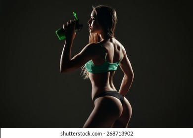 healthy young sexy woman with perfect fitness body and glutes drinking water against a black background