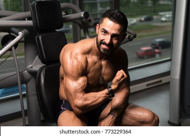 Healthy Young Tattoo Man Sitting Strong In The Gym And Flexing Muscles - Muscular Athletic Bodybuilder Fitness Model Posing After Exercises
