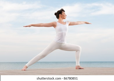 Healthy young woman doing yoga exercising outdoor at sea