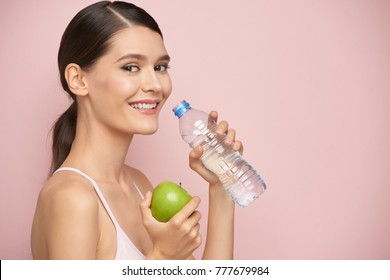 Healthy young woman drinking fresh water, isolated on pink