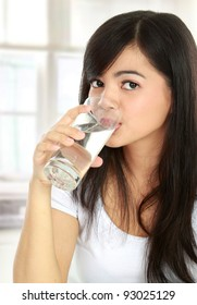 Healthy young woman drinking a glass of water