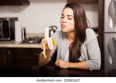 Healthy young woman eating a banana while sitting in the kitchen