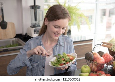 Healthy young woman eating salad in the kitchen