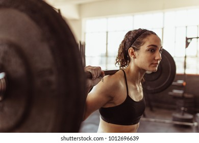 Healthy young woman at gym exercising with barbell. Fit young woman working out with heavy weights at cross training gym.