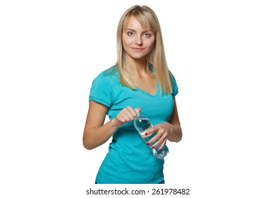 Healthy young woman holding a bottle of mineral water while isolated background