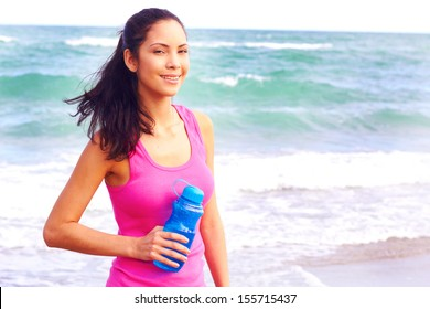 Healthy young woman holding water bottle on boardwalk. Horizontal shot.