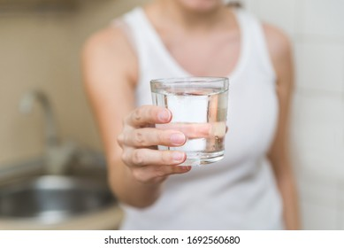 a healthy young woman holds a glass of water. clean drinking water in a clear glass in your hands close-up. water filter