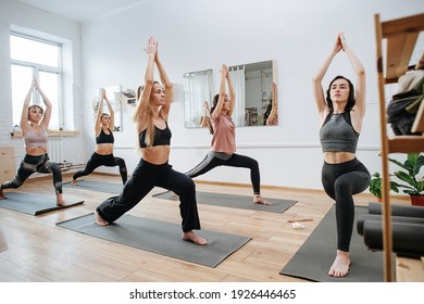 Healthy young woman practicing yoga in a group in front of an instructor. They are holding warrior asana, joining hands above head.