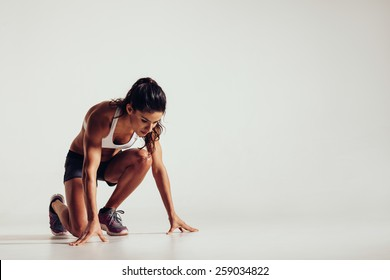 Healthy young woman preparing for a run. Fit female athlete ready for a spring over grey background with copy space.