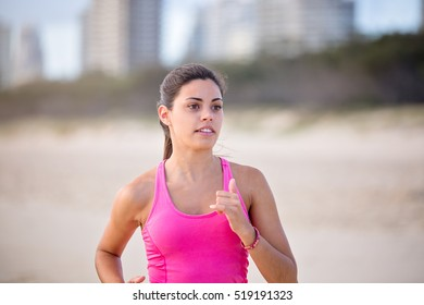 Healthy, young, woman runs along the beach feeling good and positive. She is wearing a pink sports shirt. She looks focused and determined. Focus is soft creating motion.