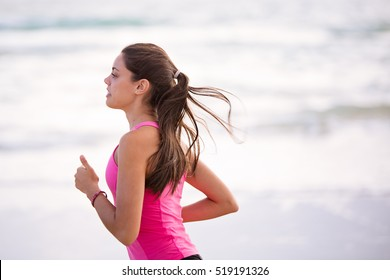 Healthy, young, woman runs along the beach. She is wearing a pink sports shirt. She looks focused and determined. Focus is soft with room for copy space.