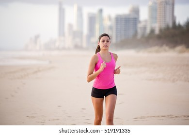Healthy, young, woman runs along the beach with Gold Coast city skyline in the background. She is wearing a pink sports shirt. She looks focused and determined. Focus is soft creating motion.
