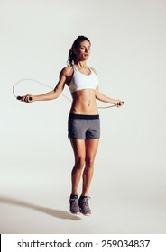Healthy young woman skipping rope in studio. Muscular young woman exercising with jumping rope on grey background.