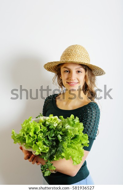 Healthy young woman in straw hat smiling with a green salad