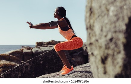 Healthy young woman stretching at seaside rocks. Fitness female warning up. Side view shot.