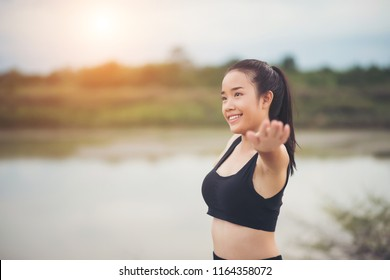 Healthy young woman warming up outdoors workout before training session at the park.
