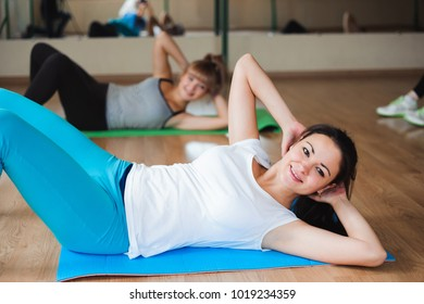 Healthy young women doing exercise on mats for fitness in the gym.