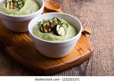 Healthy zucchini cream soup in ceramic bowls on wooden table