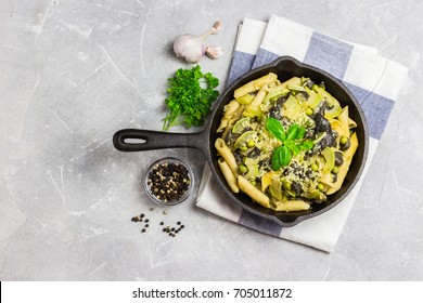 Healthy zucchini mushroom pasta in cast iron skillet.Top view, copy space.