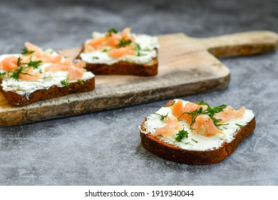 Healty salmon sandwiches with  flaxseed bread, spiced cottage cheese on  industrial background. Party food .Light keto  office lunch