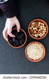 Healty, vegetarian dried fruit breakfast. Set of bowls with dried fruit to enrich a healthy vegan breakfast. Oats, almonds and plums to be included as a snack for a diet for beauty and health behavior