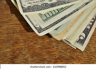 Heap of American money (US currency, USD) on the wooden background as a symbol of wealth