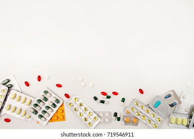 Heap of assorted various medicine tablets and pills in blisters different colors on white background. Healthcare or medicament addiction concept. Copy space.