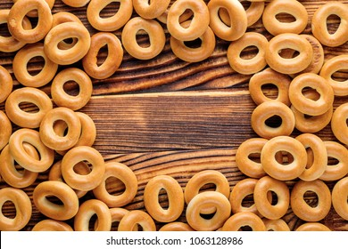 Heap of bagels scattered on the wooden table. Top view. Copy space for your text.