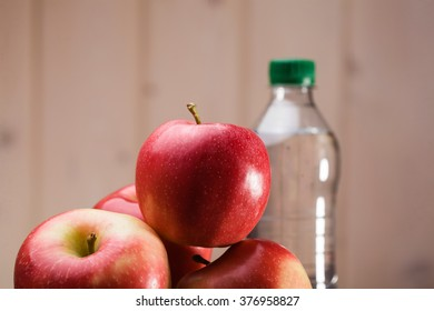 Heap of big sweet fresh red yellow apples and full bottle of water on beige wall background, horizontal photo