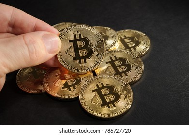 Heap of bitcoins with one bitcoin coin in hand