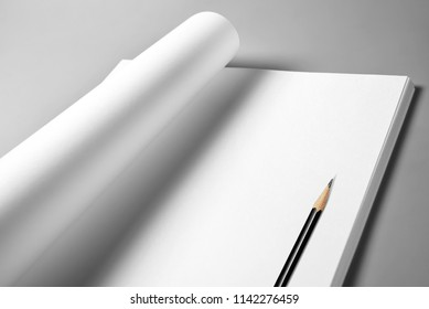 Heap of blank sheets of paper with curled upper page and pencil