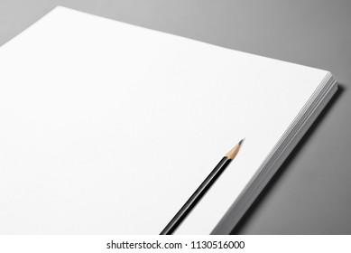 Heap of blank sheets of paper and pencil