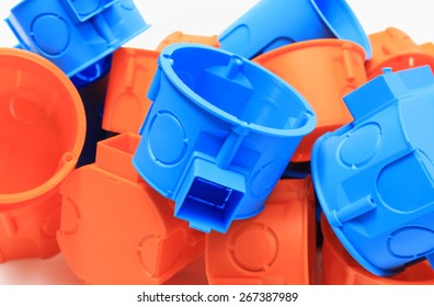 Heap of blue and orange plastic electrical boxes on white background, junction boxes, accessories for engineering jobs.