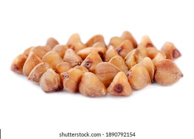 Heap of buckwheat seeds isolated on white background, closeup. Buckwheat seeds isolated on white. Buckwheat grains isolated on white background, close-up. Buckwheat for porridge.